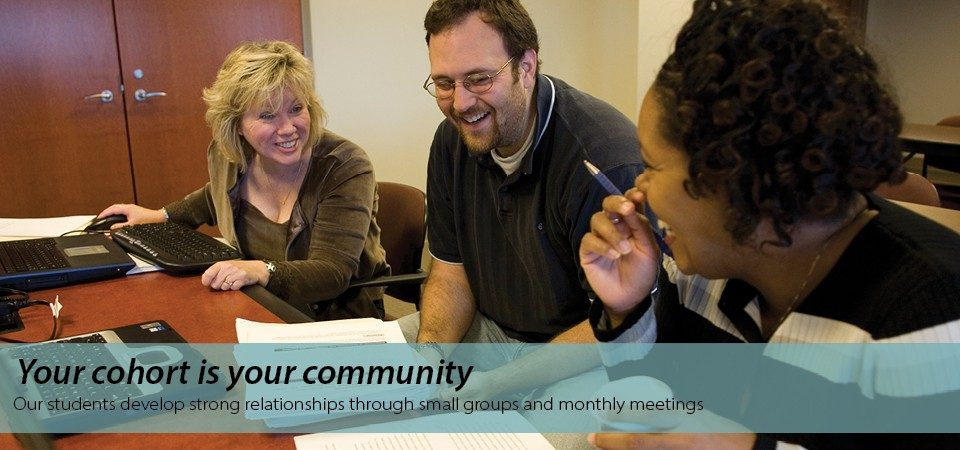 Your cohort is your community: our students develop strong relationships   through small groups and monthly meetings. Three Professional Master of Business students looking at an assignment, and talking and laughing with each other.